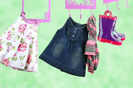 Fashion baby dresses hanging on a hanger on a green  background Stock Photo