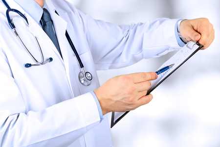 prescript: Medical doctor  with a stethoscope around his neck  holding  a black folder