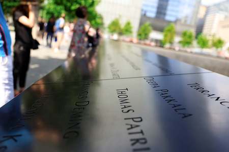 New York City, USA - August 14, 2014: 911 Memorial at Ground Zero, Manhattan, commemorating the terrorist attack of September 11, 2001. Names of victims engraved in the bronze parapet.