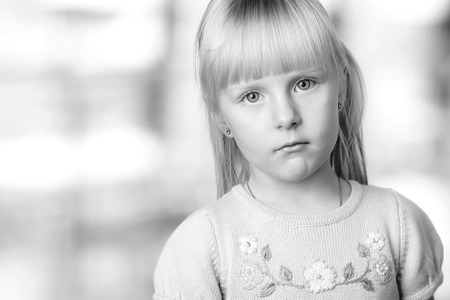 sadly: serious blond little girl looking sadly