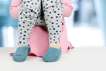 Childrens legs hanging down from a chamber-pot on a blue background