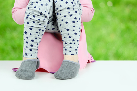 Childrens legs hanging down from a chamber-pot on a green background