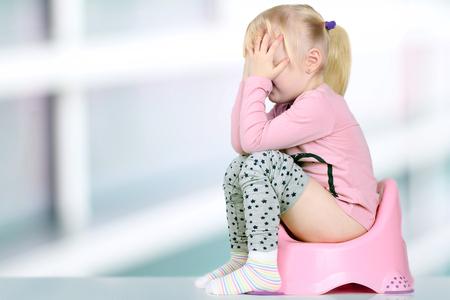 Les jambes de l'enfant qui pend à partir d'un pot de chambre sur un fond bleu Banque d'images - 65987700