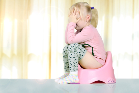 Childrens legs hanging down from a chamber-pot on a gray background Stock Photo