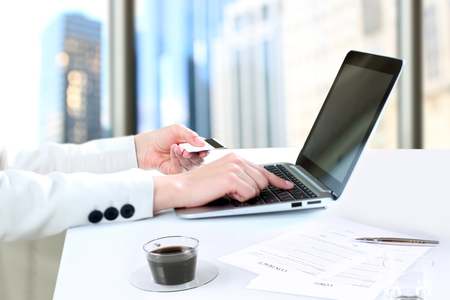 debet: Business woman  entering  data of  a credit card . On-line shopping on the internet using a laptop Stock Photo