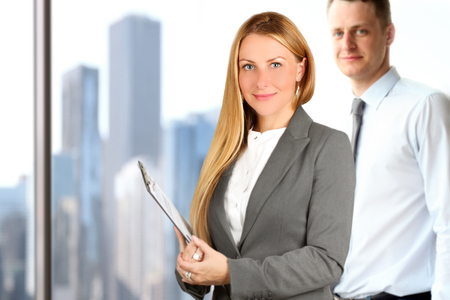 Portraits of business woman and man standing near window Stock Photo