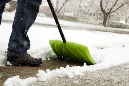 Man schaufelt und die Beseitigung von Schnee vor seinem Haus in der Vorstadt Standard-Bild - 67109094