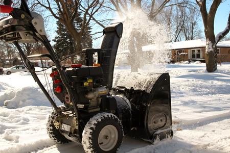 男は、歩道の除雪機が雪をクリーンアップします。 写真素材