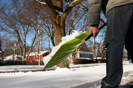 shoveling: Man shoveling and removing snow in front of his house in the suburb Stock Photo