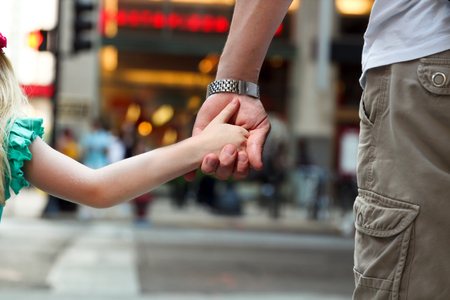 union familiar: father holding  the daughter child  hand  behind  the traffic lights Foto de archivo