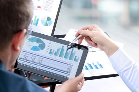 Bedrijfscollega's die en financiële cijfers aangaande een digitale tablet werken analyseren Stockfoto