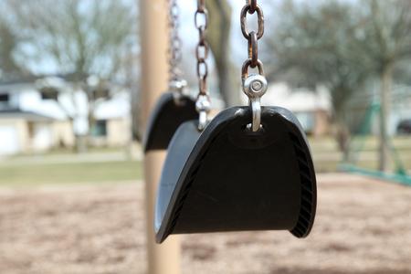 light chains: Empty Swings in a  light.