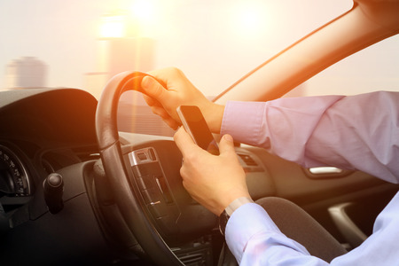 careless: The businessman using a mobile smart phone while driving the car