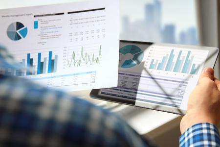Geschäftsmann, der Finanzzahlen auf einem Diagramm mit Tablet arbeitet und analysiert