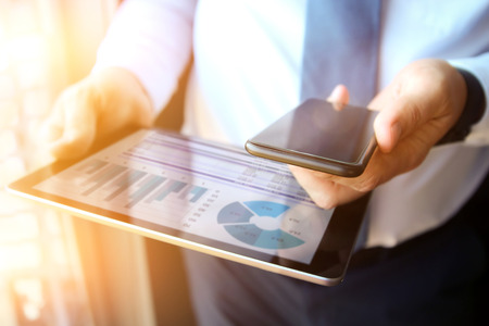 Business man working and analyzing financial figures on a graphs on a tablet and mobile phone