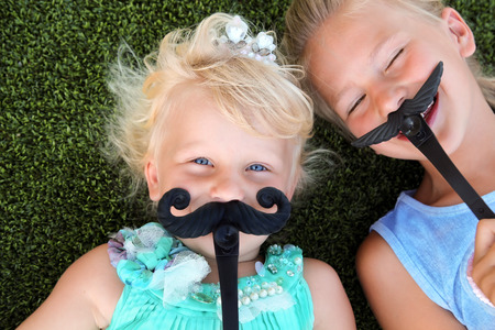 beautiful blonde smiling  girls  lying  on the grass on a summer day with mustache Stock Photo