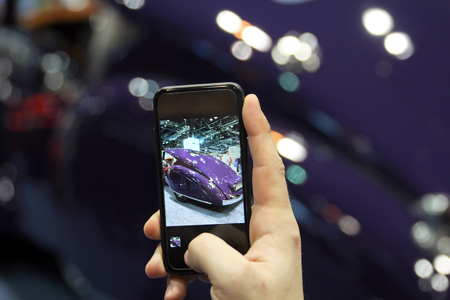 Man taking a picture a moder car at the auto show Stock Photo