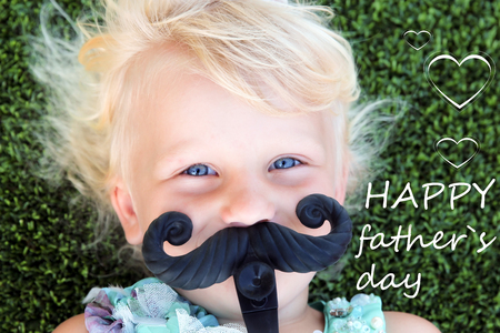 beautiful blonde girl  lying  on the grass  with mustache. Happy father`s day Stock Photo