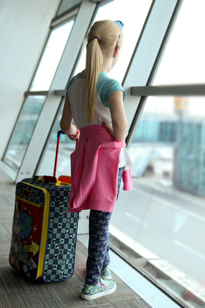 Blonde girl is standing near window at  the airport