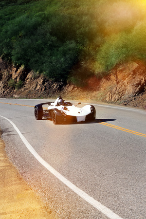 White modern sport car is driving on empty countryside asphalt road at sunset