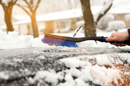 Transportation, winter  and vehicle concept - man cleaning snow from car with brush Standard-Bild - 112592151