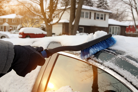 Transportation, winter  and vehicle concept - man cleaning snow from car with brush Stock Photo