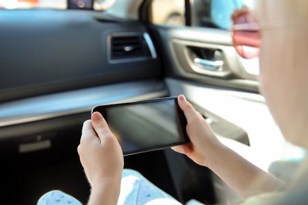 Little girl chi ld sitting in a car with a smartphone in a hands Stock Photo