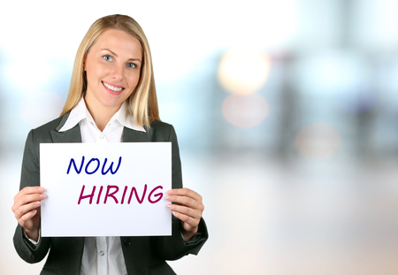 Happy businesswoman holding a white banner  NOW HIRING and smiling Stock Photo