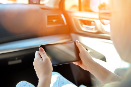 Little girl child sitting in a car with a smartphone in a hands Stock Photo
