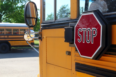 The Yellow school bus with stop sign Standard-Bild - 112592227