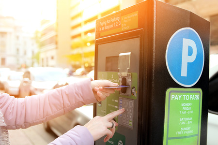 woman is paying his parking using credit card at  parking pay station terminal Stock Photo