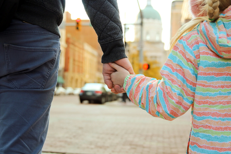 father holding  the daughter child  hand  behind  the traffic lights Stock Photo
