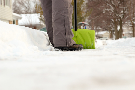 Man shoveling and removing snow in front of his house in the suburb Stock Photo