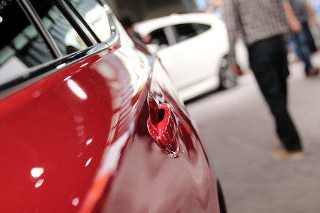 Modern red car. Car handle. Auto show