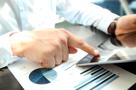 Business man working and analyzing financial figures on a graphs using tablet Stock Photo