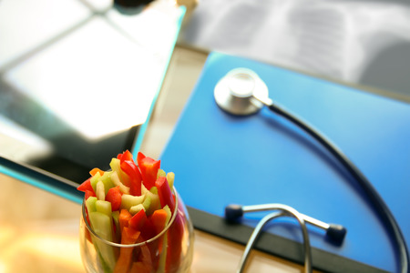 stethoscope, vegetable and x-ray in the office Stock Photo