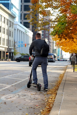 Close up image of a man on an electric scooter in the street Stock Photo