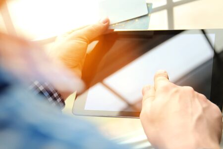 business man entering data of a credit card . On-line shopping on the internet using a tablet Standard-Bild - 149826211