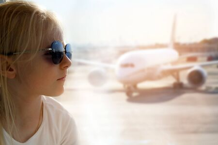 Blonde girl is sitting  near window at  the airport