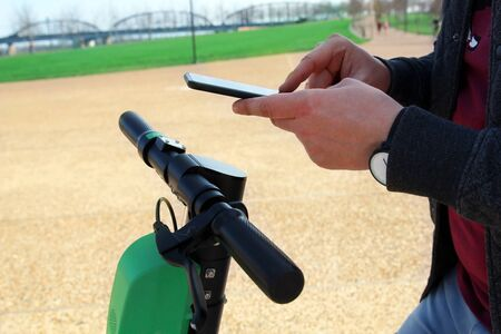 Close up image of a man on an electric scooter paying online