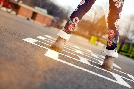 Girl in beautiful boots Playing Hopscotch On Playground Outdoors Standard-Bild - 149806879