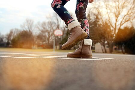 Girl in beautiful boots Playing Hopscotch On Playground Outdoors