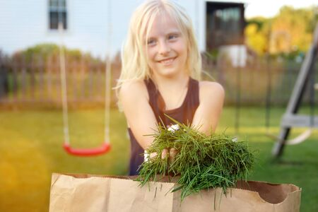 girl gathering grass into the package