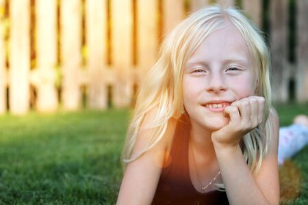 beautiful blonde smiling  girl  lying  on the grass on a summer day Standard-Bild - 149883004