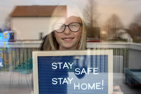 Stay home quarantine coronavirus pandemic prevention. Beautiful girl stays near the open window Standard-Bild - 149883009
