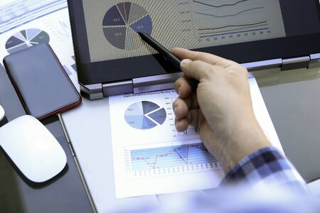 Business man working and analyzing financial figures on a graphs using laptop and tablet Standard-Bild