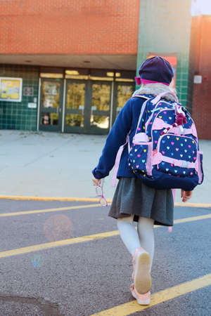 School girl is going to school with backpack