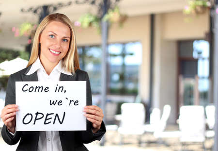 Happy woman holding a white banner with welcome sign. Come in, we are open