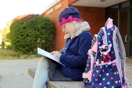 Beautiful girl sitting near with school outside.Back to school