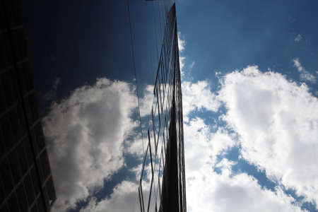 the skyscraper in a modern city with a blue sky. Reflection
